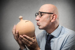 Businessman kissing his piggy-bank stock images