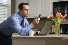 Businessman in kitchen. Royalty Free Stock Photos