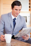 Businessman in the kitchen reading news and having coffee Stock Photos