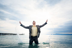 Businessman Knee-deep In Water. Young businessman is standing knee-deep in water Stock Images
