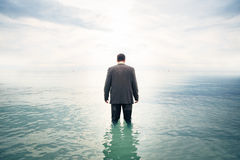 Businessman Knee-deep In Water. Young businessman is standing knee-deep in water Royalty Free Stock Photos