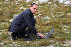 Businessman kneeling. Young businessman kneeling in nature with his laptop royalty free stock image
