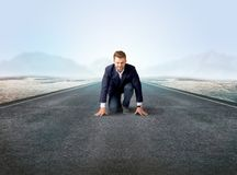 Businessman kneeling in ready position. Young determined businessman kneeling before blank running track Royalty Free Stock Image