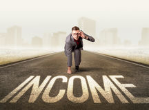 Businessman kneeling in ready position. Young determined businessman kneeling before income sign Royalty Free Stock Images