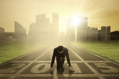 Businessman kneeling on track. Man kneeling on track and ready to chase his dream in the future 2015 Stock Photos