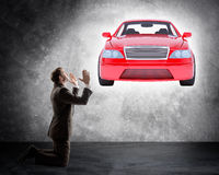 Businessman on knees in front of car Royalty Free Stock Images