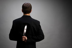 Businessman with knife Stock Images