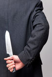 Businessman with a knife behind his back. royalty free stock photography