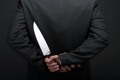 Businessman with knife in hand Royalty Free Stock Image