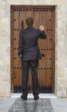 Businessman knocking at a door Stock Image