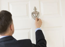 Businessman Knocking Door Knocker. Rear view of mature businessman knocking door knocker royalty free stock photography