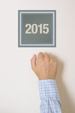 Businessman knocking on door with number 2015. Happy New Year conceptual image, celebration at the door Royalty Free Stock Photo