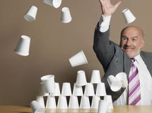 Businessman Knocking Down Pyramid Of Cups Royalty Free Stock Photo