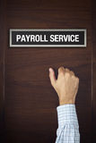 Businessman is knocking on Payroll service door Stock Photo