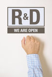 Businessman knocking on Research and Development department door Royalty Free Stock Image