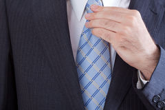 Businessman knotting his tie Stock Images