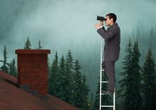 Businessman on ladder with binoculars over roof and forest. Digital composite of Businessman on ladder with binoculars over roof and forest Royalty Free Stock Photos