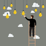 Businessman on the ladder catching a light bulb idea Stock Photography
