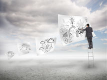 Businessman on a ladder drawing on a floating paper Stock Photo
