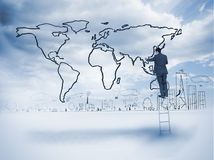 Businessman on a ladder drawing a map Stock Photo