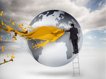 Businessman on a ladder drawing on a planet with paint Stock Images