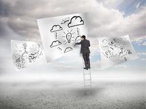 Businessman on a ladder drawing a process Royalty Free Stock Image