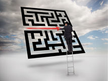 Businessman on ladder drawing red line through qr code Stock Image
