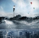 Businessman on a ladder escapes from crisis and looking for a new way Royalty Free Stock Photo