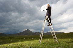 Businessman On Ladder Holding Blank Sign Royalty Free Stock Photography