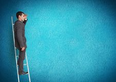Businessman on ladder looking at a distance Stock Photography