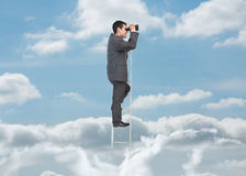 Businessman on ladder over the clouds Stock Images