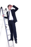 Businessman on ladder searching for possibilities Stock Photo