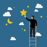 Businessman on the ladder trying to catch the star Stock Photo