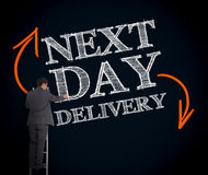 Businessman on ladder writing next day delivery Stock Photo
