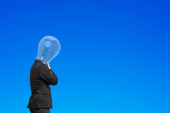 Businessman with lamp head chin in hand, thinking Royalty Free Stock Photo