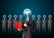 Businessman with lamp-head have got an idea. Male businessman with lamp-head and laptop have got an idea Royalty Free Stock Images