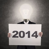 Businessman with lamp-head showing year 2014 Stock Photo
