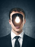 Businessman with lamp inside his head on the gray Stock Photos