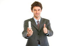 Businessman with lamp showing thumbs up Royalty Free Stock Photo