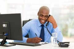 Businessman landline phone. Happy african businessman talking on landline phone and writing report Royalty Free Stock Images