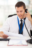 Businessman landline phone. Businessman talking on landline phone looking at business documents handheld Stock Photo