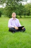 Businessman with laptop. On the green grass in the park Royalty Free Stock Image