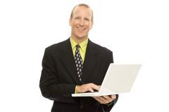 Businessman with laptop. A businessman in a suit holds a laptop and smiles Stock Photography