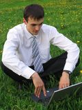 Businessman with laptop. Sitting on the grass Royalty Free Stock Photography