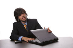 Businessman with laptop. Handsome young businessman opening or closing laptop computer on desk; white studio background royalty free stock photo
