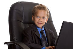 Businessman with laptop. Young boy dressed as businessman with laptop Royalty Free Stock Image