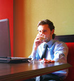 Businessman with laptop. Businessman is sitting in a bar with a notebook on the table and coffee with cream Stock Photography
