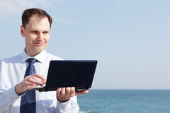 Businessman with laptop against sea stock photography