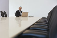 Businessman With Laptop In Board Room Stock Photos