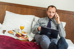 Businessman with laptop during breakfast. He is lying on bed. Royalty Free Stock Photos